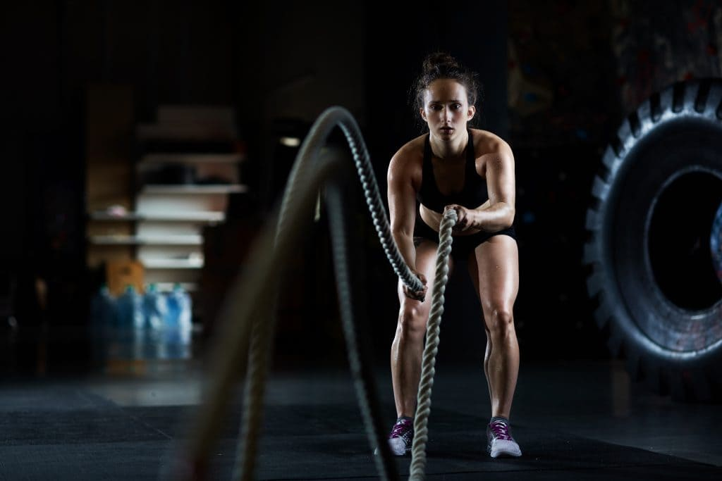 Young woman doing battle rope exercises in gym