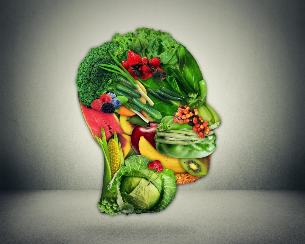 Healthy lifestyle choice concept. Fresh green vegetables and fruit shaped as human head face as symbol of good nutrition.